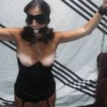 The wife knelling in bondage showing her tits..