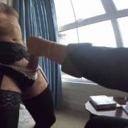 Hubby likes to wear wife's lingerie, stockings, suspenders and sexy panties while she gives him a handjob in the hotel window