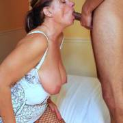 Mature 54 year young hotwife on her knees servicing the cock of a man half her age.