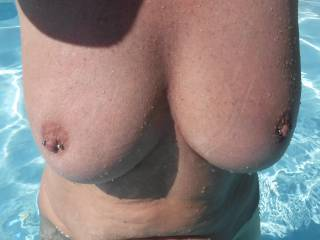 Another pic of my big tits with their pierced nipples, in the swimming pool at home.  I hope you like?