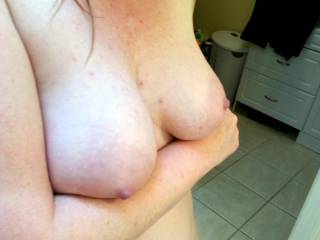 Holding up my breasts... would you like to hold them?