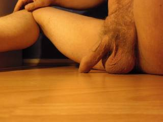 I\'m sitting on the floor. My dick and balls (which both need a hair trim) are resting on the floor and some pre-cum is is coming out!
