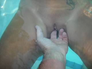 Playing with my wife\'s lovely smooth pierced pussy in the swimming pool at home.