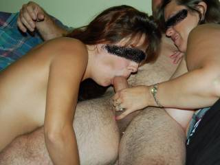 So hot watching a hot wife jerk her man's nice, thick cock into another sexy woman's mouth.  Awesome pic.  We'd love to join that action.