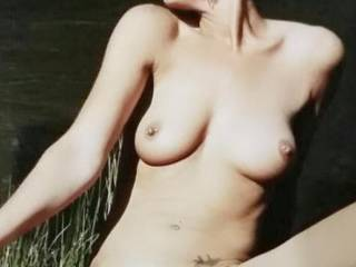 Posing nude outdoors by the river