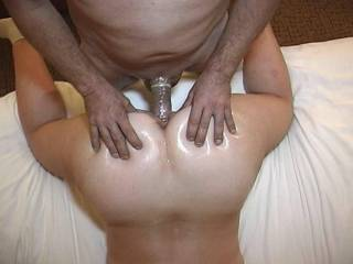 Another top view of the wife\'s oiled up ass in the air getting fucked by a friend as he squeezes those juicy ass cheeks on a hotel room bed