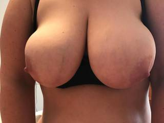 My wife's huge all natural boobs spilling over the tops of her sexy shelf bra.