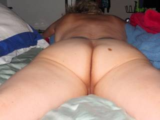Naked on a bed...ass exposed and facing up...pussy showing...damn I like this picture!