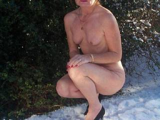 Hot stuff out in the snow. Good looking woman in an attractive pose. Love that red hair and those darling breasts.