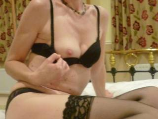 black lingerie with stockings and a little flash of tit