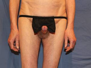 The loincloth is raised to reveal an erection with a shiny swollen glans and a pair of hairy balls.