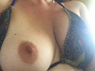She is a horny fuck.. another picture from while on vacation, exposing her boob in public, erect nipple and tan lines on display.
