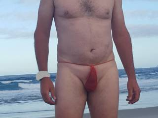 Showing off my smooth cock in a red G-string at the beach. Got a few looks. Would you look?