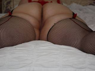 on the bed in a hot lace top and fishnets