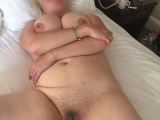 Holding her tits up so that we can all get a nice view. I have the camera in one hand and my cock in the other. Can you blame me?