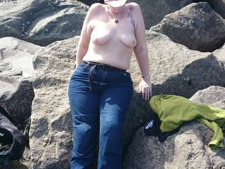 Top less on the beach against the sea defence.
