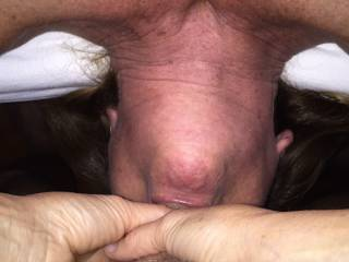 Wife swallowing cock deep, her head draped over side of bed opening her throat for all of my cock's cum load