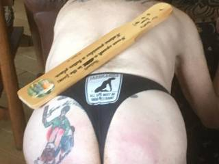 """My wife designed and required me to get this """"Spare the Paddle; Spoil the Husband"""" tattoo;  the paddle is used by her to great effect;  and the """"leash law strictly """" thong was purchased by her."""