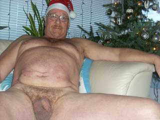 Happy under the Christmastree with my hat, big belly, big smile and tiny dick