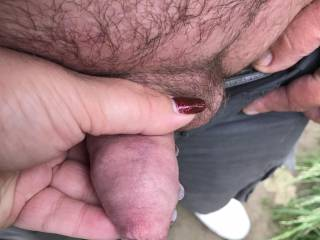 Holding his small dick in public.