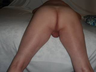 Bent over the edge of the bed