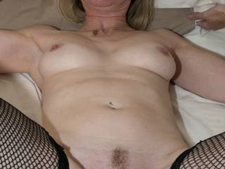 I am laying on my bed, ready to be fucked. Would you like to fuck my wet pussy while my husband watches? Tell me what you would do to me.