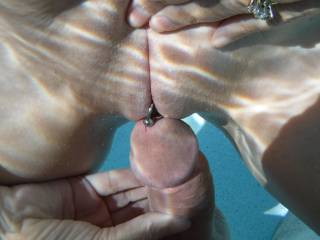 Playing with his semi-hard cock in the swimming pool at home. Teasing him, by rubbing his cock-head over my smooth shaven, pierced pussy.