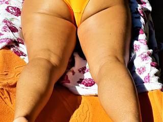 tanned ass in tangerine bikini showing cheeks