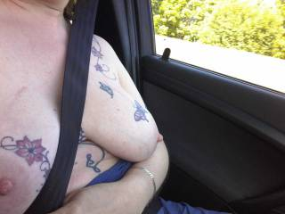 Tits fully on show as Sally sits in the car as we drive along the highways and byways of Southern England.