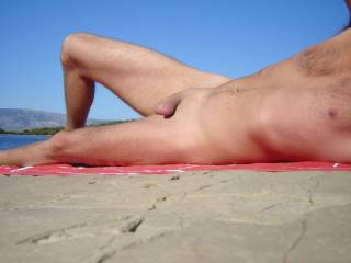 I love being on a beach naked.   I would love to be there with you, playing with your smooth body and cock...