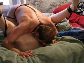 Wearing a leather harness I\'ve got her pinned down with my face in her crotch in a 69 .position
