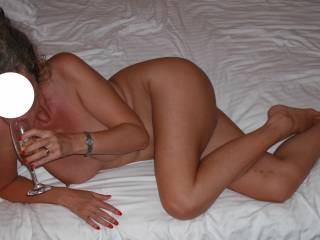 My beautiful wife on the bed at a hotel in Europe, sipping Champagne before our threesome.