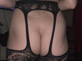 Rear view of my bum in all in one stockings and suspenders.