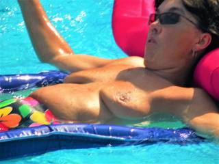 Mature wife floating around the pool naked, letting all the boys in the neighborhood see her.