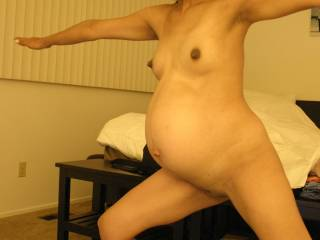 9 months pregnant asian wife doing yoga