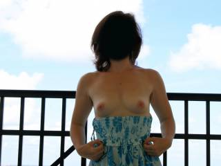 Flashing her tits on the balcony.