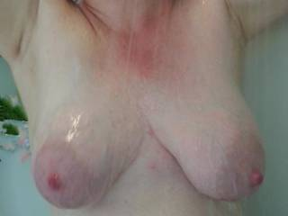 Hands up, glistening milk filled tits on display