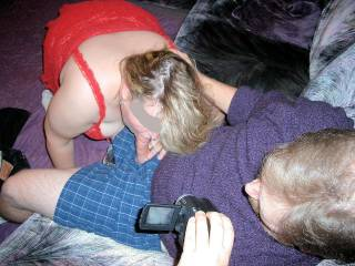 Wife & I bring this guy home after the swinger party we attended. In no time my wife is on her knees taking his thick cock to the back of her throat. I hand him the video camera for some POV video of his cock in her mouth & I take photos of them together.