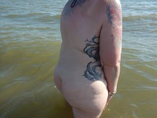 Mrs venturing in to the water on a nudist beach
