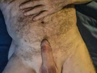 Lying down about to masturbate.