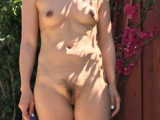 Her in our backyard. It was a beautiful sunny day and she was in her bikini. We thought because of the sunny day, the pics would look extra nice. She loves being naked outside so she stripped down while I took a few pics. She is happy with the results.