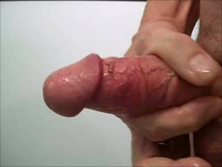 Clear close up of muscled, veined, fat cock spewing creamy white cum.